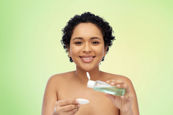 beauty, skin care and cosmetcs concept - portrait of happy smiling young african american woman with cotton pad and clensing lotion or skin toner in bottle over green natural